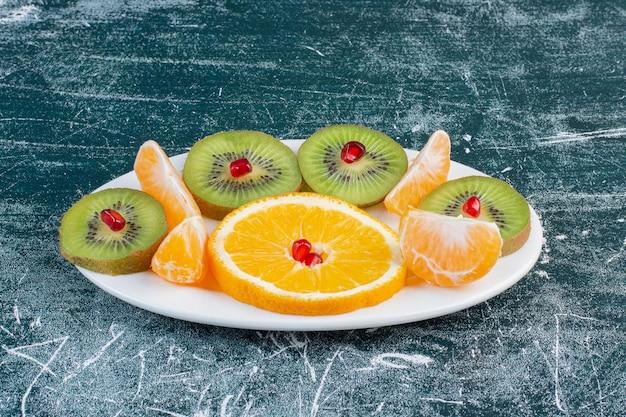 Bandeja de frutas com frutas sazonais picadas e fatiadas.