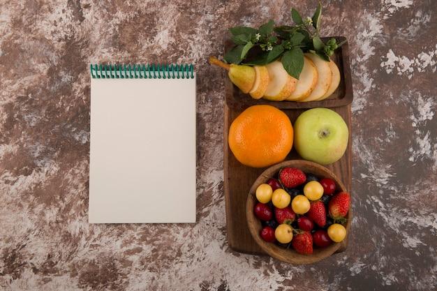 Bandeja de frutas com hortelã no mármore com um caderno de lado