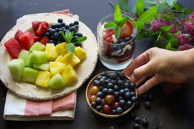 Bandeja de frutas com morangos, mirtilos, abacaxi, melancia e melão em fundo escuro