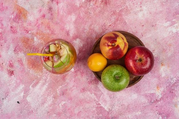 Bandeja de frutas com uma xícara de suco.