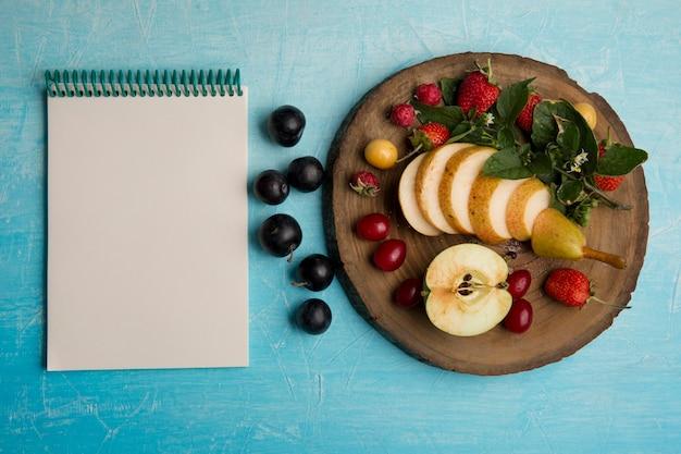 Bandeja de frutas redonda com peras, maçã e frutas vermelhas com um caderno à parte