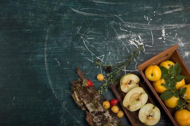 Bandeja de frutas redonda com peras, maçã e frutas vermelhas em um fundo fosco, no canto