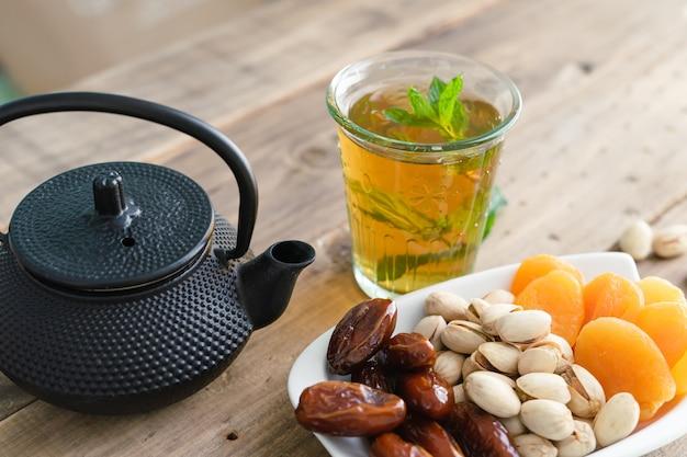 Bandeja de frutas secas com copo de chá em fundo de madeira. copie o espaço. vista de perto. comida.