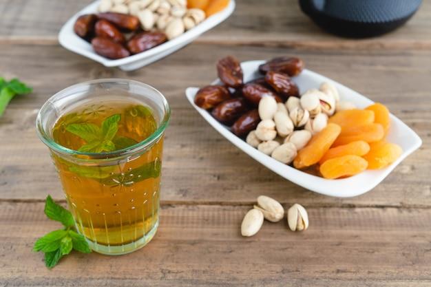 Bandeja de frutas secas com copo de chá em fundo de madeira. copie o espaço.