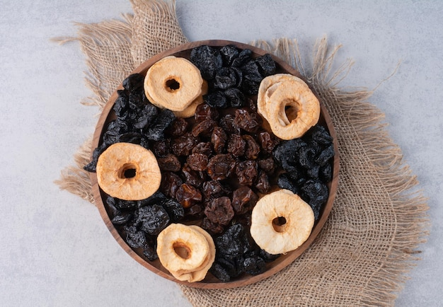 Bandeja de frutas secas com fatias de maçã, uvas passas e cerejas.