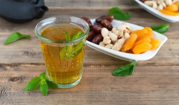 Bandeja de frutas secas com tâmaras, pistache e damascos secos com copo de chá sobre fundo de madeira. copie o espaço.