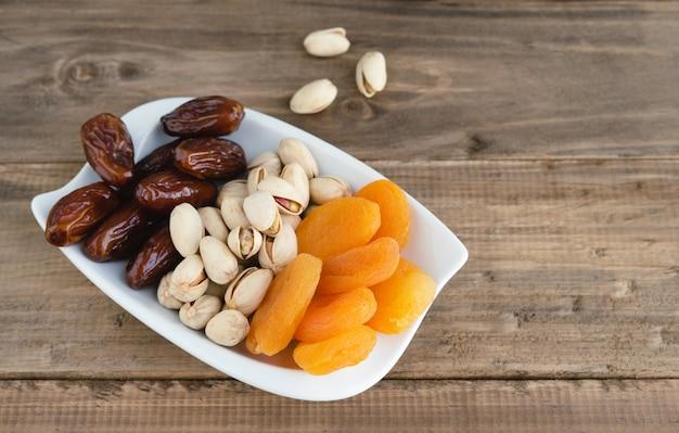 Bandeja de frutas secas com tâmaras, pistache e damascos secos sobre base de madeira. copie o espaço.