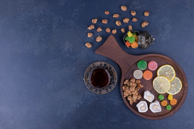 Bandeja de lanche de madeira com geleias e um copo de chá no meio