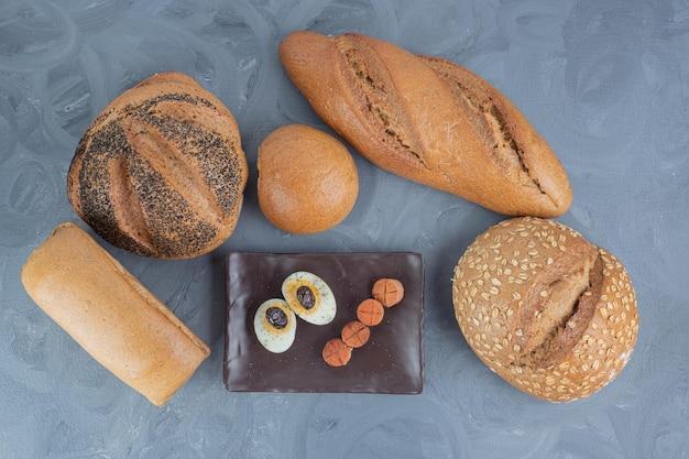 Bandeja de linguiça e fatias de ovo ao lado de pães na mesa de mármore.