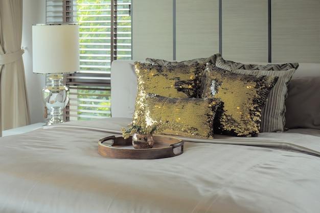 Bandeja de madeira com almofadas de glitter dourado na cama