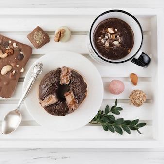 Bandeja de madeira com café da manhã e variedade de chocolate no plano leigos