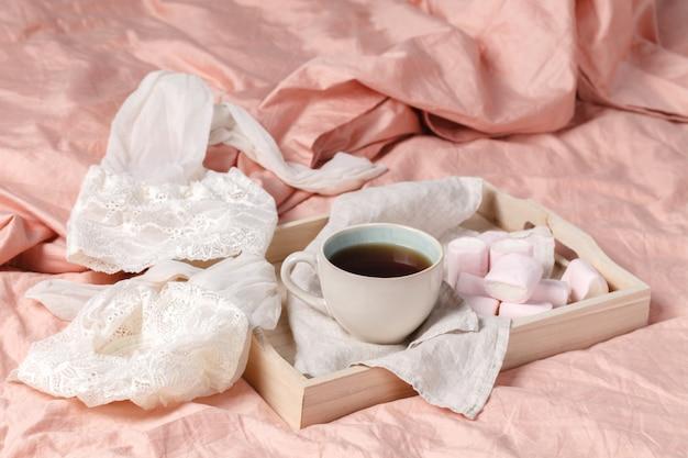 Bandeja de madeira com café da manhã leve na cama em cima da cama com lençóis brancos