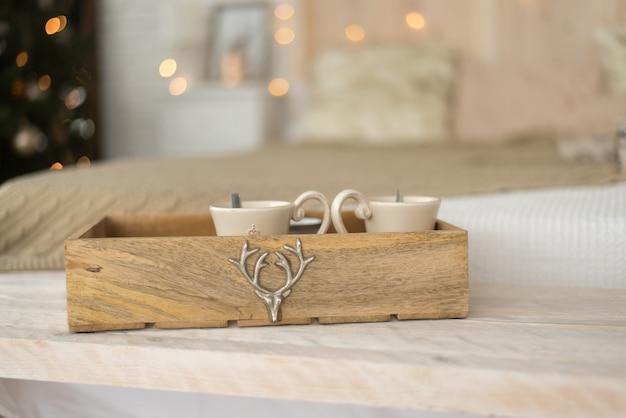 Bandeja de madeira com canecas no fundo da cama.