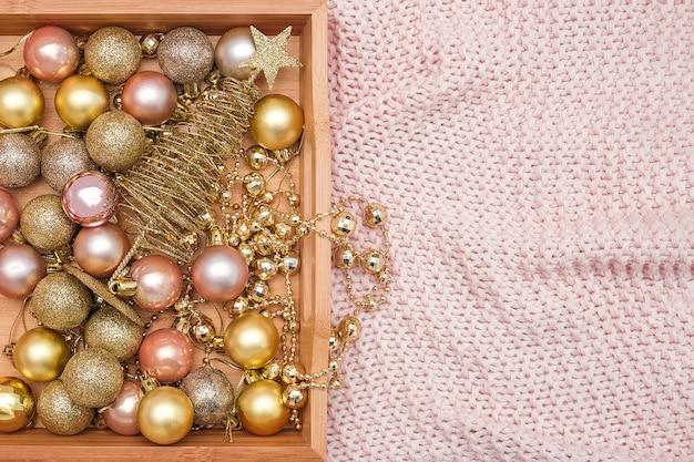 Bandeja de madeira com decorações de natal na manta rosa de malha quente. natal ou ano novo.