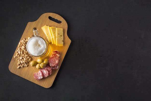 Bandeja de madeira com delicioso lanche indo bem com cerveja
