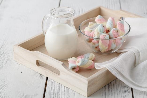 Bandeja de madeira com um copo de leite e marshmallow