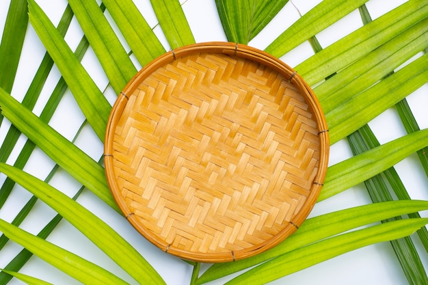 Bandeja de madeira de bambu na superfície de folhas verdes