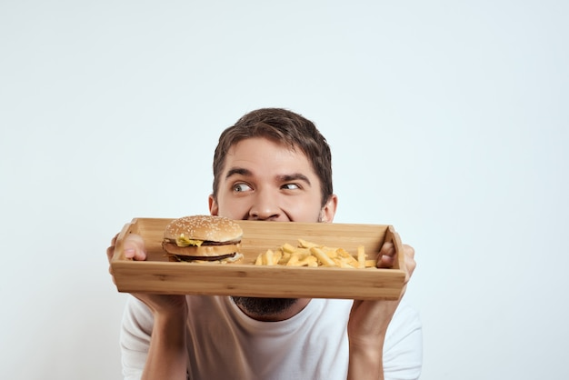 Bandeja de madeira de homem barbudo com hambúrgueres de batata frita divertidos com cerveja fast food