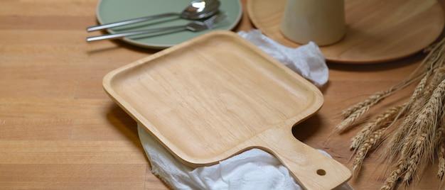Bandeja de madeira mock-up acima de guardanapos brancos na mesa de jantar de madeira com conjunto de jantar e decorações