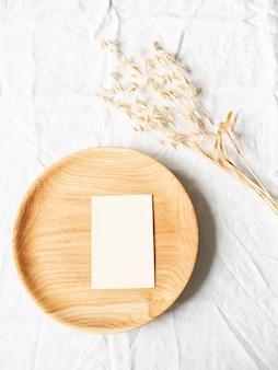 Bandeja de madeira redonda para artesanato com papel timbrado em branco e orelhas de aveia secas