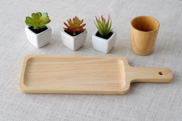 Bandeja de madeira vazia e pequenos vasos de árvores no fundo do mantel de mesa