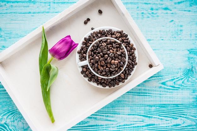 Bandeja de madeira vintage com xícara de porcelana cheia de grãos de café e flores rosa