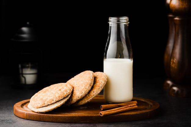 Bandeja de madeira vista frontal com biscoitos e leite