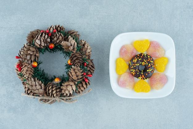 Bandeja de marmeladas e um donut ao lado de uma coroa de pinha no mármore.