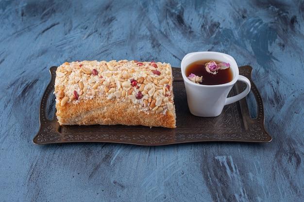 Bandeja de metal com bolo de rolo de frutas e xícara de chá preto sobre superfície de mármore.