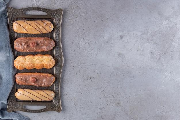 Bandeja de metal de doces saborosos éclairs na mesa de pedra.