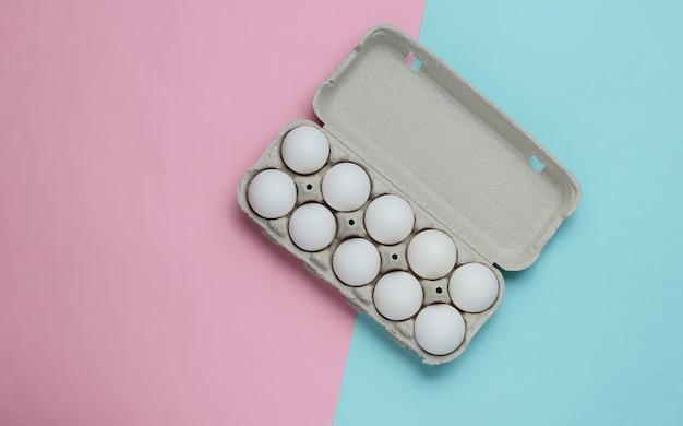 Bandeja de papelão com ovos em fundo rosa azul pastel. conceito de culinária minimalista