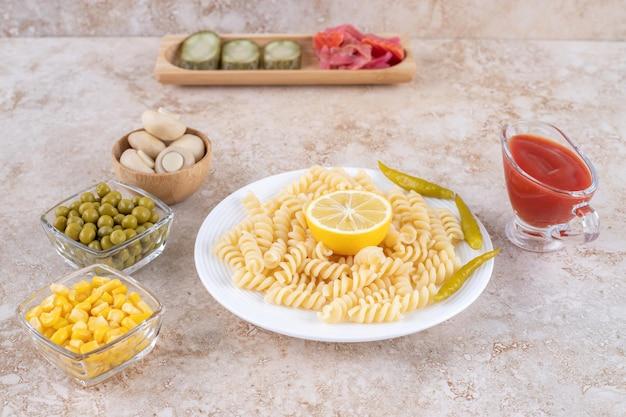 Bandeja de pickle, tigelas de vegetais, copo de ketchup e prato de macarrão em superfície de mármore.