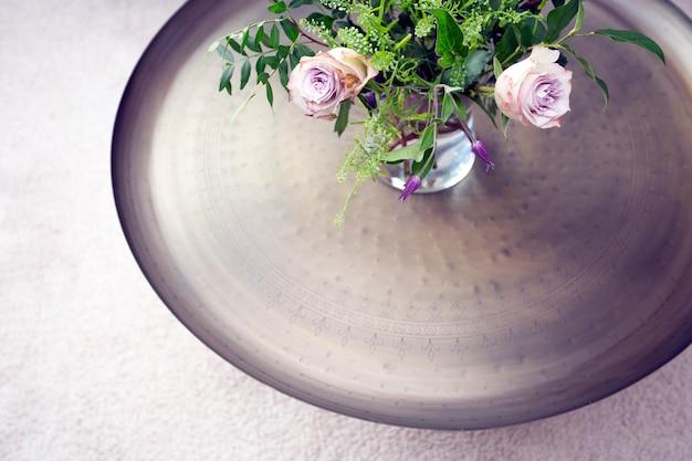 Bandeja de prata com rosas roxas em vaso sobre uma mesa contra a vista superior do tapete de luxo, interior bonito da decoração