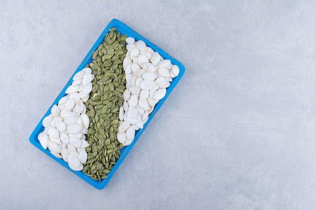 Bandeja de servir azul cheia de sementes de abóbora brancas e pepitas na superfície de mármore