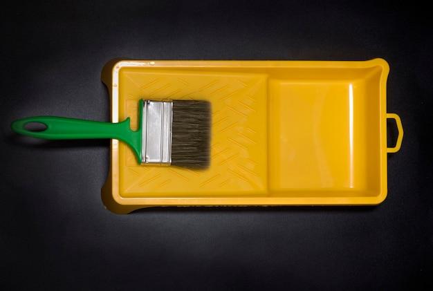 Bandeja de tinta vazia amarela, com pincel em fundo preto.