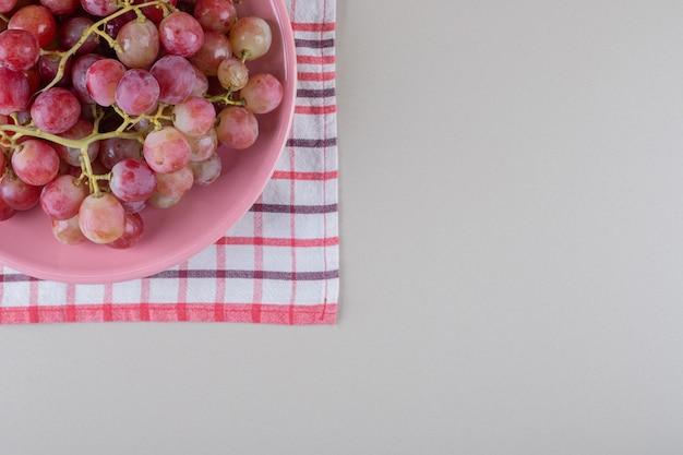 Bandeja de uvas em uma toalha sobre mármore