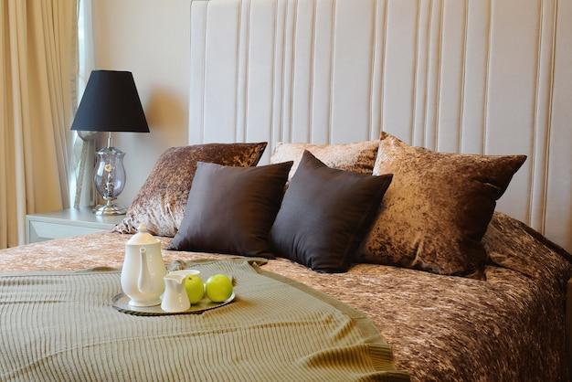 Bandeja decorativa com grupo de chá e maçã verde na cama para o café da manhã.