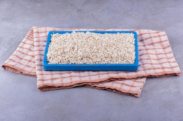 Bandeja grande com aveia empilhada por cima, sobre uma toalha com fundo de mármore. foto de alta qualidade