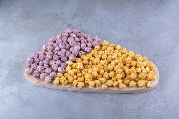 Bandeja grande com dois tipos de doces de pipoca empilhados na superfície de mármore
