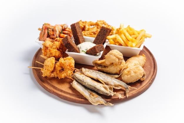 Bandeja isolada de cerveja de frutos do mar fritos com peixes e camarões na placa de madeira