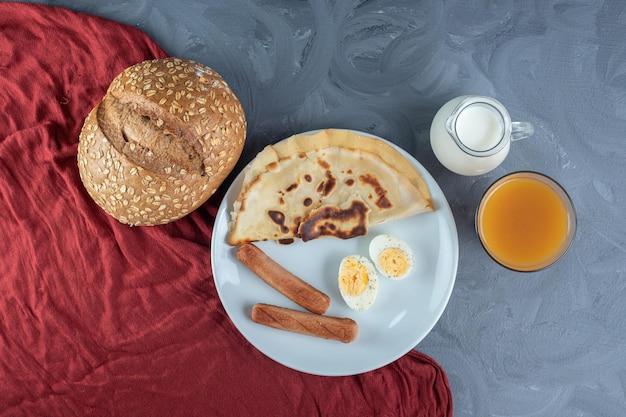 Bandeja modesta de panqueca, salsichas e fatias de ovo cozido ao lado de leite, suco e pão na mesa de mármore.