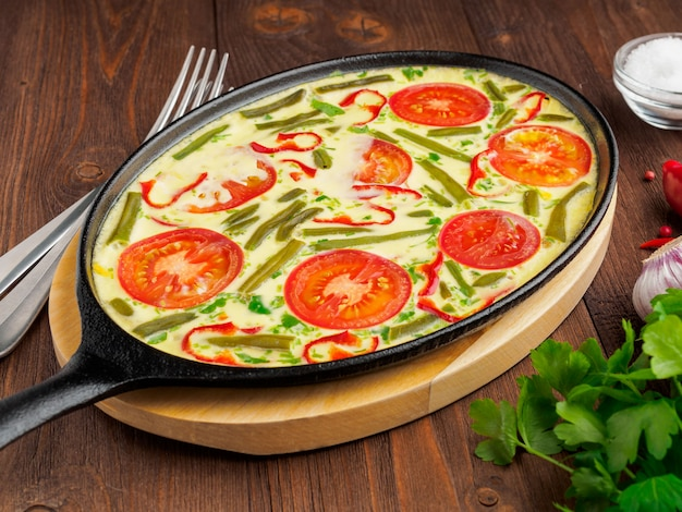 Bandeja oval do ferro fundido com a omeleta quente deliciosa com tomates. fundo de textura de madeira marrom