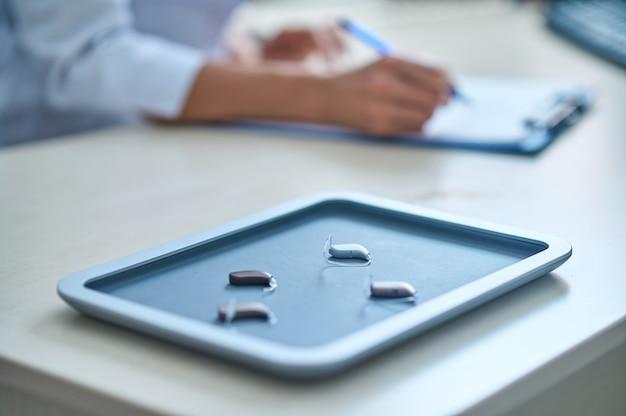 Bandeja para aparelho auditivo na mesa do otorrinolaringologista