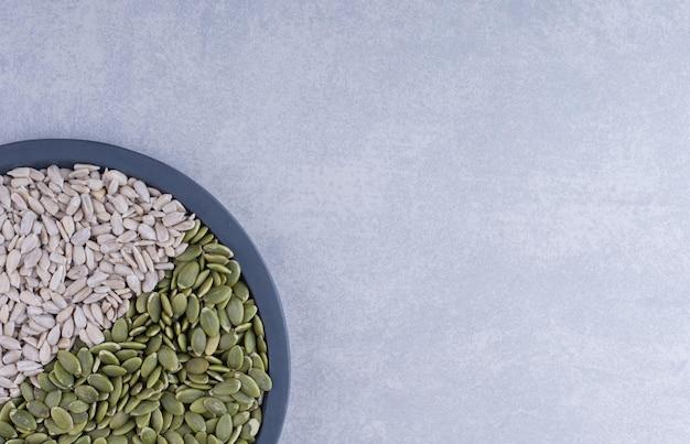 Bandeja pequena cheia de sementes de girassol descascadas e pepitas na superfície de mármore