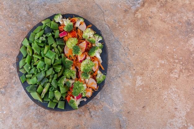 Bandeja pequena com salada mista de vegetais e grãos de feijão picados em superfície de mármore