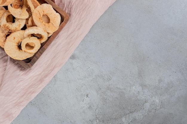 Bandeja pequena de anéis de maçã frita na mesa de concreto.