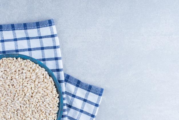 Bandeja pequena e azul sobre uma toalha dobrada, cheia de arroz de grão curto sobre fundo de mármore.