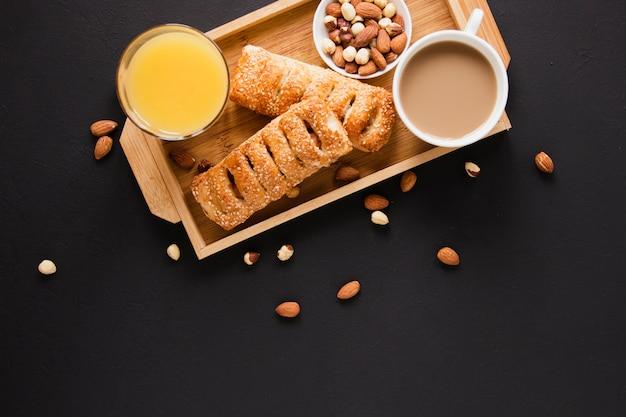 Bandeja plana leigos com nozes de pastelaria misture café e suco de laranja