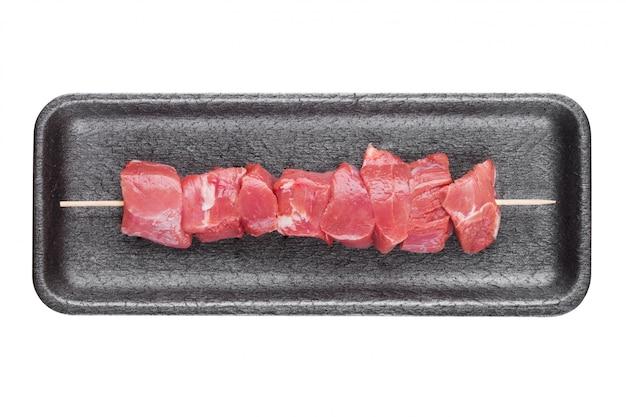Bandeja plástica com espetada de carne de porco crua fresca na vara de madeira
