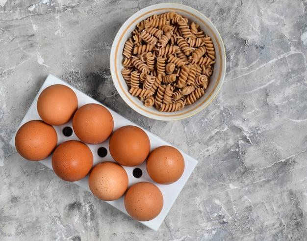 Bandeja plástica com ovos de galinha, tigela com grãos inteiros de macarrão em um fundo cinza e concreto. vista do topo